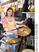Купить «Adult girl selecting drums and accessories», фото № 22595036, снято 21 июля 2019 г. (c) Яков Филимонов / Фотобанк Лори