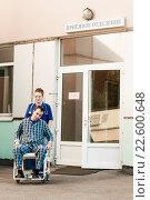 Улыбающаяся женщина медицинский работник сопровождает мужчину пациента на кресле каталке в приемное отделение больницы, фото № 22600648, снято 20 сентября 2014 г. (c) Эдуард Паравян / Фотобанк Лори