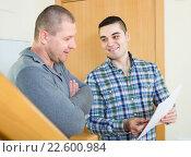 Купить «Service employee with tenant at doorway», фото № 22600984, снято 18 августа 2018 г. (c) Яков Филимонов / Фотобанк Лори