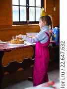 Девушка в праздничном колпаке вставляет свечи в торт на день рождения. Стоковое фото, фотограф Анна Кирьякова / Фотобанк Лори