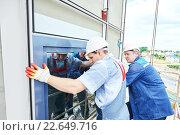 Купить «builders worker installing glass windows on facade», фото № 22649716, снято 29 июня 2015 г. (c) Дмитрий Калиновский / Фотобанк Лори