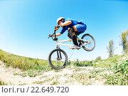 Купить «cyclist riding jumping with bicycle cross-country», фото № 22649720, снято 25 августа 2015 г. (c) Дмитрий Калиновский / Фотобанк Лори