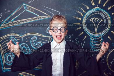 Радостный мальчик в очках у школьной доски с рисунками