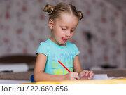 Купить «Девочка с двумя хвостиками старательно выполняет уроки», фото № 22660656, снято 25 марта 2016 г. (c) Виктория Ковелина / Фотобанк Лори