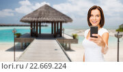 happy woman taking picture by smartphone on beach. Стоковое фото, фотограф Syda Productions / Фотобанк Лори