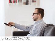 Купить «smiling man with tv remote control at home», фото № 22670132, снято 19 марта 2016 г. (c) Syda Productions / Фотобанк Лори