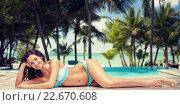 Купить «happy woman in bikini tanning over summer beach», фото № 22670608, снято 14 апреля 2015 г. (c) Syda Productions / Фотобанк Лори