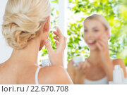 Купить «close up of woman applying face cream at bathroom», фото № 22670708, снято 13 февраля 2016 г. (c) Syda Productions / Фотобанк Лори