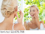 close up of woman applying face cream at bathroom. Стоковое фото, фотограф Syda Productions / Фотобанк Лори
