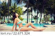 Купить «happy woman in bikini tanning over summer beach», фото № 22671324, снято 14 апреля 2015 г. (c) Syda Productions / Фотобанк Лори