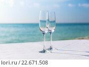 close up of two champagne glasses on beach. Стоковое фото, фотограф Syda Productions / Фотобанк Лори