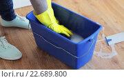 Купить «woman washing and squeezing rag in bucket at home», видеоролик № 22689800, снято 17 апреля 2016 г. (c) Syda Productions / Фотобанк Лори