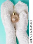 Купить «Руки в белых шерстяных варежках держат елочную игрушку», фото № 22690364, снято 29 ноября 2015 г. (c) Рамиль Гибадуллин / Фотобанк Лори