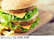 Купить «close up of hamburger or cheeseburger on table», фото № 22698548, снято 21 мая 2015 г. (c) Syda Productions / Фотобанк Лори