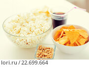 Купить «close up of popcorn and corn crisps or nachos», фото № 22699664, снято 21 мая 2015 г. (c) Syda Productions / Фотобанк Лори