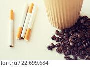 Купить «close up of cigarettes, coffee cup and beans», фото № 22699684, снято 22 мая 2015 г. (c) Syda Productions / Фотобанк Лори