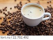 Купить «close up coffee cup and grains on wooden table», фото № 22702492, снято 7 апреля 2016 г. (c) Syda Productions / Фотобанк Лори