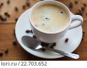 Купить «close up coffee cup and grains on wooden table», фото № 22703652, снято 7 апреля 2016 г. (c) Syda Productions / Фотобанк Лори