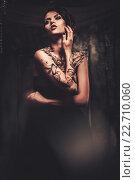 Купить «Tattooed beautiful woman in old spooky interior», фото № 22710060, снято 19 июля 2014 г. (c) Andrejs Pidjass / Фотобанк Лори