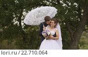 Купить «Жених обнимает невесту под белым зонтиком», видеоролик № 22710064, снято 12 апреля 2016 г. (c) Mikhail Davidovich / Фотобанк Лори