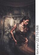 Купить «Tattooed beautiful woman in old spooky interior», фото № 22710068, снято 19 июля 2014 г. (c) Andrejs Pidjass / Фотобанк Лори