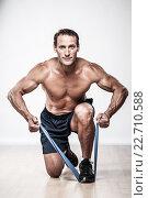 Купить «Handsome muscular man doing stretching exercise», фото № 22710588, снято 31 июля 2011 г. (c) Andrejs Pidjass / Фотобанк Лори