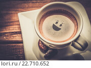 Купить «Coffee cup on a wooden table with smiley in it», фото № 22710652, снято 21 января 2014 г. (c) Andrejs Pidjass / Фотобанк Лори