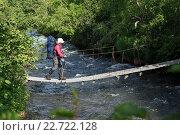 Купить «Девушка-туристка с рюкзаком переправляется через горную реку по висячему мосту», фото № 22722128, снято 11 июля 2014 г. (c) А. А. Пирагис / Фотобанк Лори