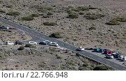 Купить «White vehicle driving on asphalt road in mountain valley, aerial view. TF-21 route with turn to Teide Cable car. Tenerife, Canary, Spain», видеоролик № 22766948, снято 18 февраля 2016 г. (c) Кекяляйнен Андрей / Фотобанк Лори