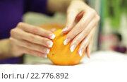 Купить «Девушка с французским маникюром держит апельсин», видеоролик № 22776892, снято 17 марта 2014 г. (c) Валентин Беспалов / Фотобанк Лори
