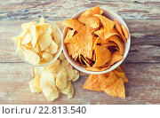 Купить «close up of potato crisps and corn nachos on table», фото № 22813540, снято 22 мая 2015 г. (c) Syda Productions / Фотобанк Лори