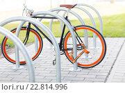 Купить «close up of bicycle locked at street parking», фото № 22814996, снято 30 мая 2015 г. (c) Syda Productions / Фотобанк Лори