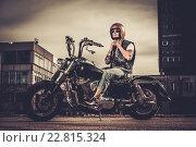 Купить «Tattooed biker and his bobber style motorcycle on a city streets», фото № 22815324, снято 10 апреля 2015 г. (c) Andrejs Pidjass / Фотобанк Лори