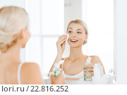 Купить «young woman with lotion washing face at bathroom», фото № 22816252, снято 13 февраля 2016 г. (c) Syda Productions / Фотобанк Лори