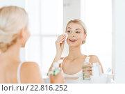 Купить «young woman with lotion washing face at bathroom», фото № 22816252, снято 13 февраля 2016 г. (c) Syda Productions / Фотобанк Лори