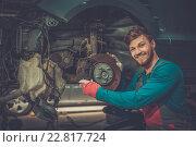 Mechanic checking car brake system in a workshop. Стоковое фото, фотограф Andrejs Pidjass / Фотобанк Лори