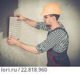 Купить «Builder applying tile on a wall», фото № 22818960, снято 18 декабря 2014 г. (c) Andrejs Pidjass / Фотобанк Лори
