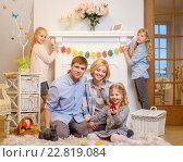 Купить «Cheerful family having fun on carpet and playing with cute bunny.», фото № 22819084, снято 3 февраля 2016 г. (c) Andrejs Pidjass / Фотобанк Лори