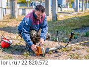 Рабочий заводит газонокосилку (2016 год). Редакционное фото, фотограф Станислав Илюк / Фотобанк Лори