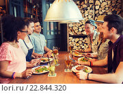 happy friends eating and drinking at bar or pub. Стоковое фото, фотограф Syda Productions / Фотобанк Лори