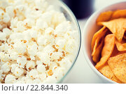 Купить «close up of popcorn and corn crisps or nachos», фото № 22844340, снято 21 мая 2015 г. (c) Syda Productions / Фотобанк Лори