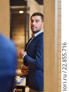 Купить «man trying jacket on at mirror in clothing store», фото № 22855716, снято 1 апреля 2016 г. (c) Syda Productions / Фотобанк Лори