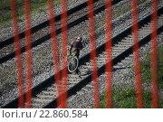 Купить «Вид через ограждение моста на мужчину с велосипедом, пересекающего железнодорожные пути в неположенном месте», фото № 22860584, снято 14 мая 2016 г. (c) Сайганов Александр / Фотобанк Лори
