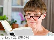 Купить «Innenaufnahme Kopf-und-Schulter-Porträt einer älteren Frau mit Lesebrille und offenem buch freundlich in die Kamera lächelnd», фото № 22898676, снято 20 января 2019 г. (c) age Fotostock / Фотобанк Лори