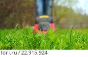 Купить «На переднем плане нескошенная трава в фокусе. На заднем расфокусированном плане приближается мужчина с газонокосилкой.», видеоролик № 22915924, снято 6 мая 2016 г. (c) Георгий Дзюра / Фотобанк Лори
