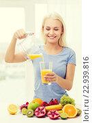 Купить «smiling woman pouring fruit juice to glass at home», фото № 22939816, снято 26 апреля 2015 г. (c) Syda Productions / Фотобанк Лори