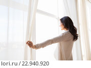 Купить «close up of pregnant woman opening window curtains», фото № 22940920, снято 23 марта 2016 г. (c) Syda Productions / Фотобанк Лори