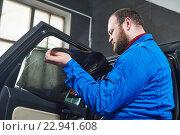 Купить «car tinting. Automobile mechanic technician applying foil», фото № 22941608, снято 14 апреля 2016 г. (c) Дмитрий Калиновский / Фотобанк Лори