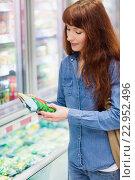 Купить «Customer picking a product in the frozen aisle», фото № 22952496, снято 15 октября 2015 г. (c) Wavebreak Media / Фотобанк Лори
