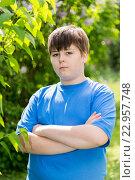 Купить «The boy crossed his arms in summer park», фото № 22957748, снято 15 мая 2016 г. (c) Володина Ольга / Фотобанк Лори